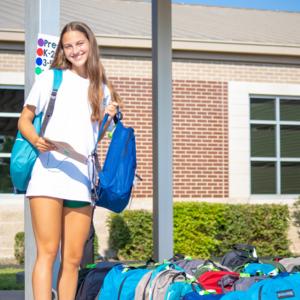 teen girl standing amid stack of backpacks