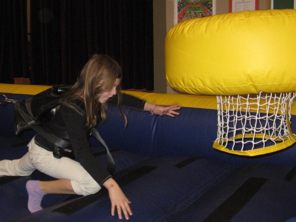girl in harness playing game on inflatable mat