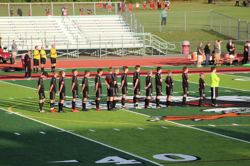 Soccer players standing in a row during the National Anthem