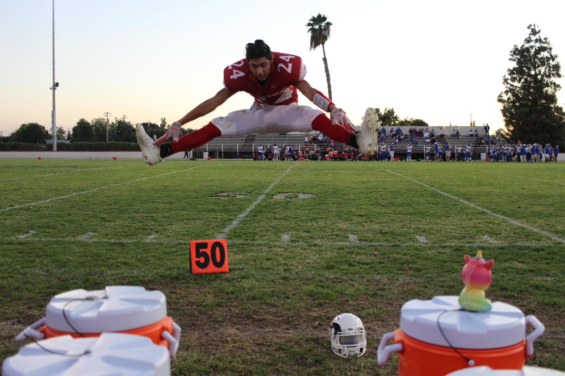 a football player doing a toe touch jump
