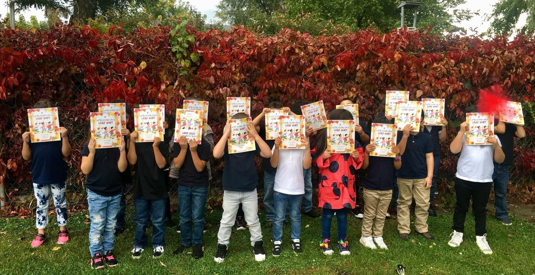 A group of kindergarten students are showing their donated books for the month of October.