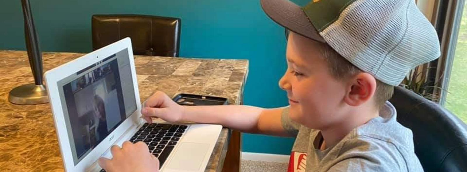 student smiles while learning online from home