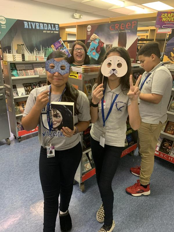 two female students holding masks while ms. Papa photobombs in the back of them