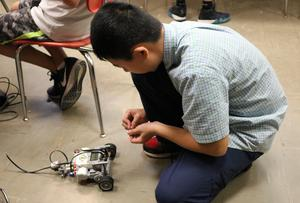 A STEM camper tests a robot he built during STEM Camp.