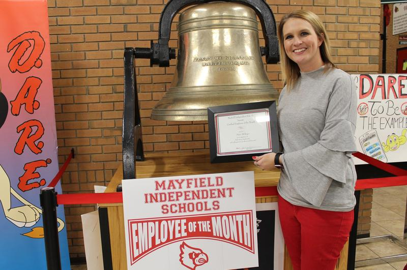 Nicole McGregor, one of two employees of the month for January, standing with award in front of bell at MMS