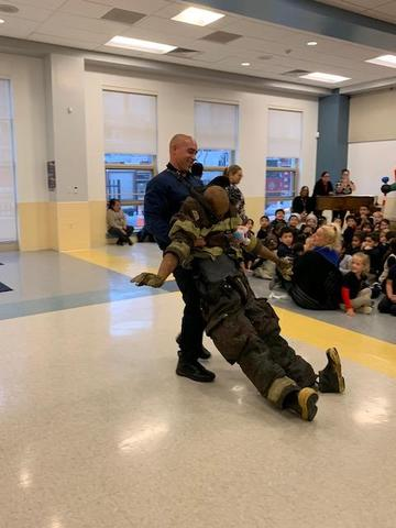 fireman showing the students how they drag a firefighter in full gear