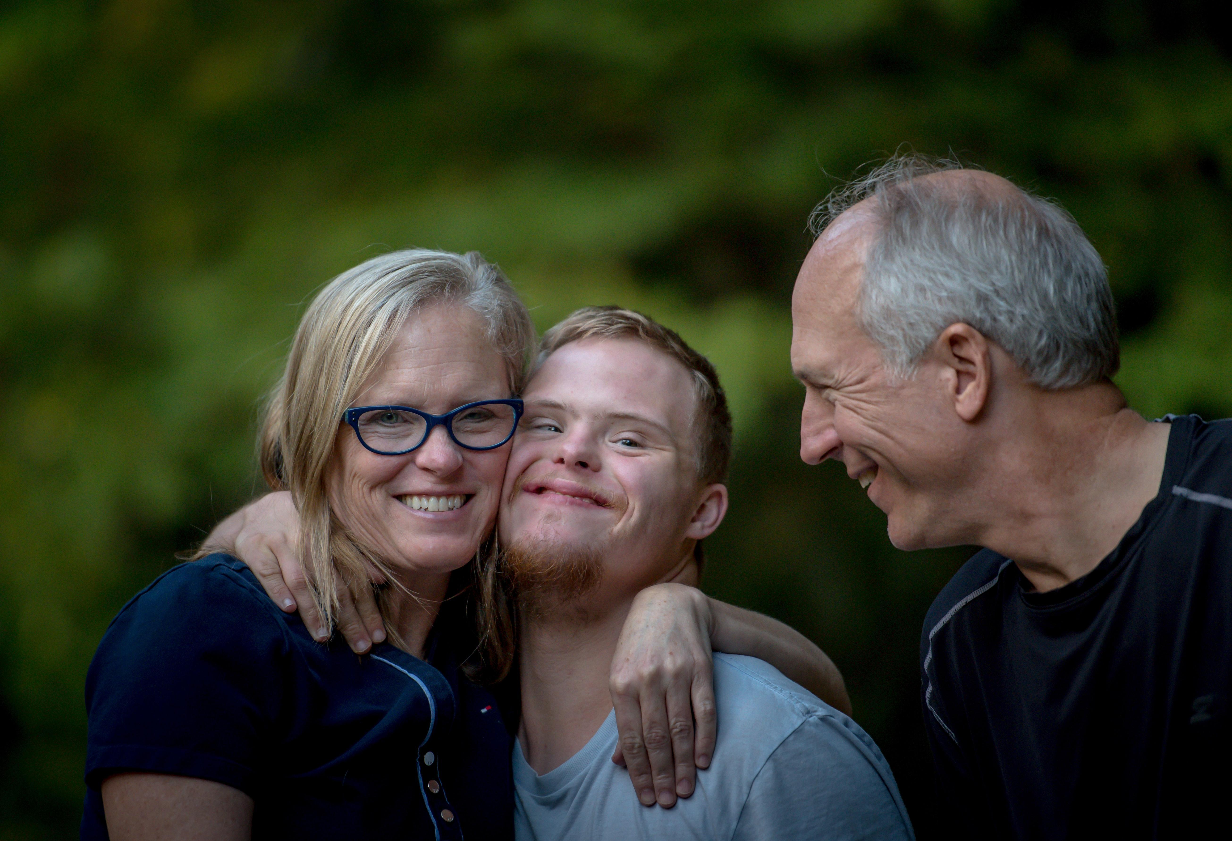 A mother hugging her adult son who has down syndrome while his father smiles at them both.