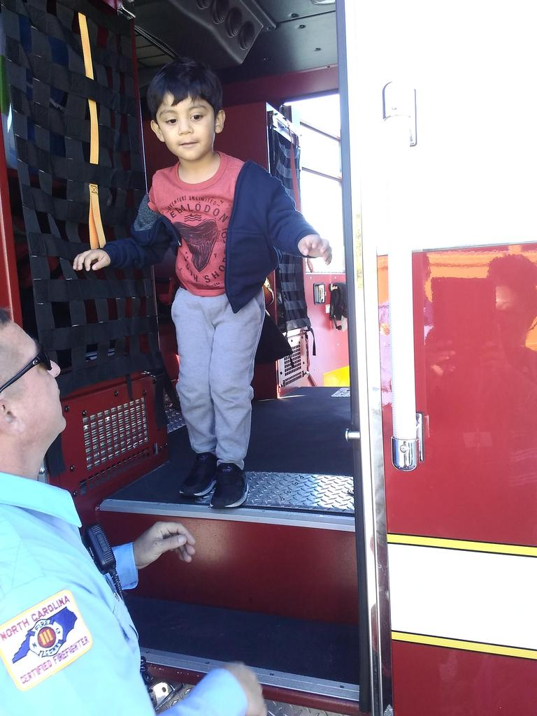 Photo of student getting off the fire truck.