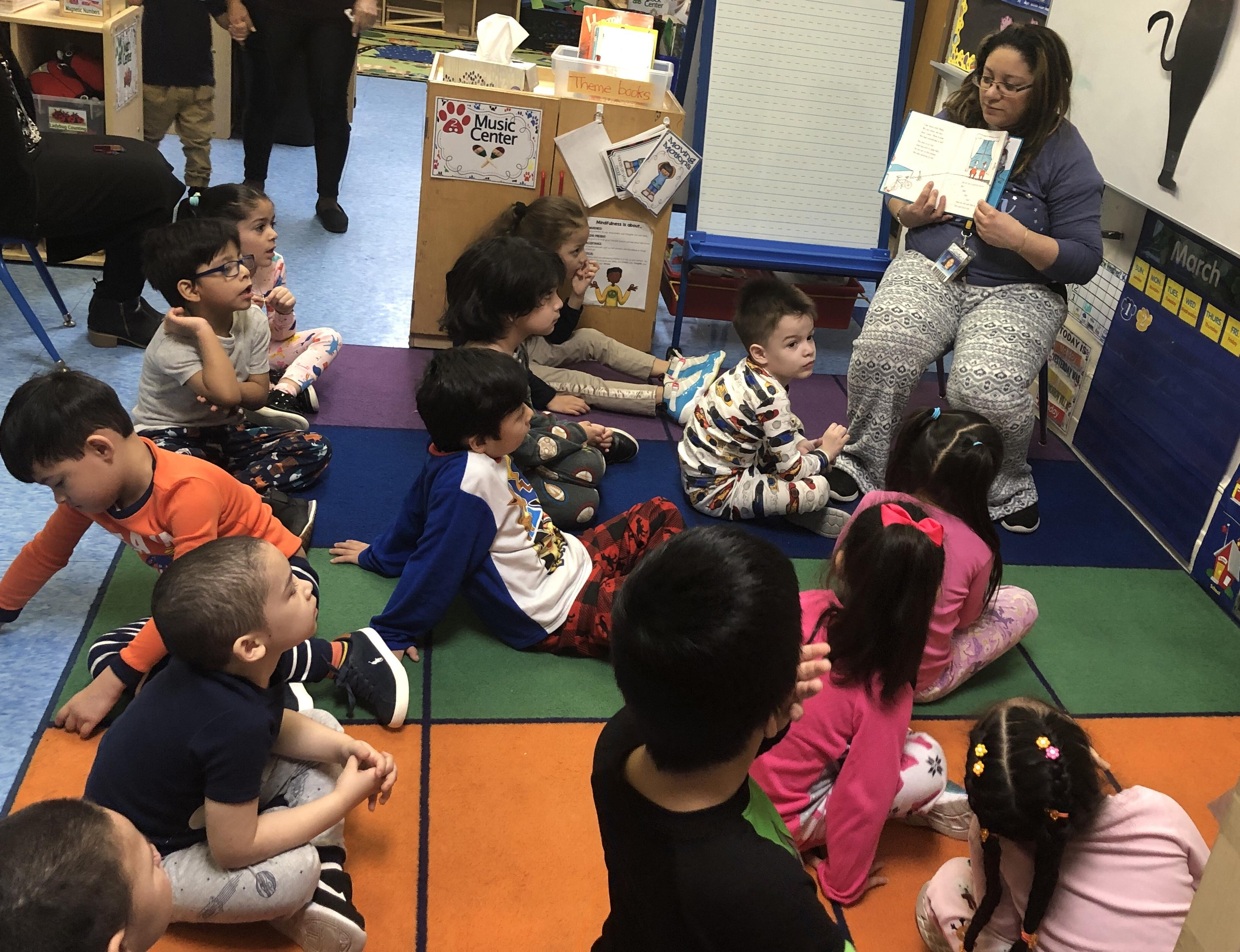 Mrs. Ortiz reading to her students wearing pjs