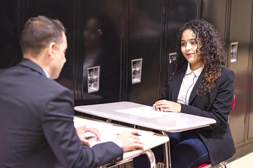 A female student, dressed in a blazer, is interviewed by School Committee member Marcony Almeida Barros