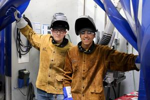 two high school males in welding gear and helmets working on a project