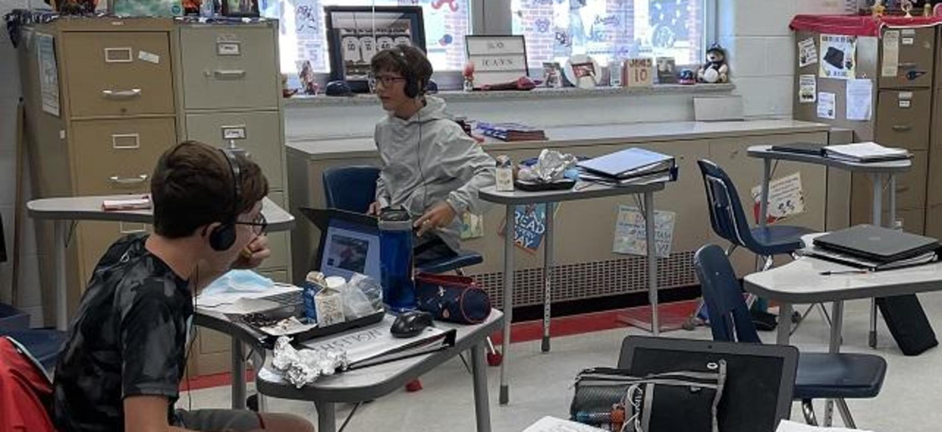 Two students work on Chromebooks in a classroom.