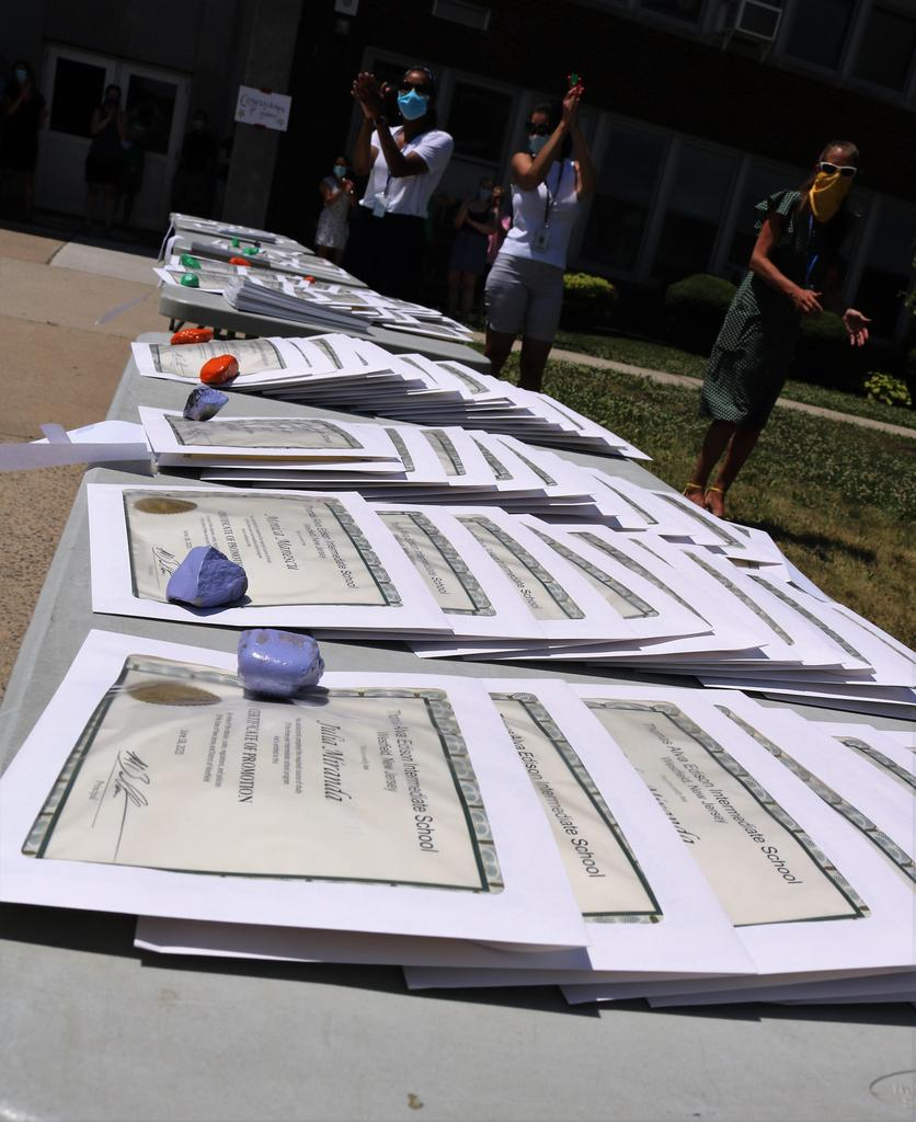 Photo of 8th grade promotion certificates on table with applauding teachers in background.