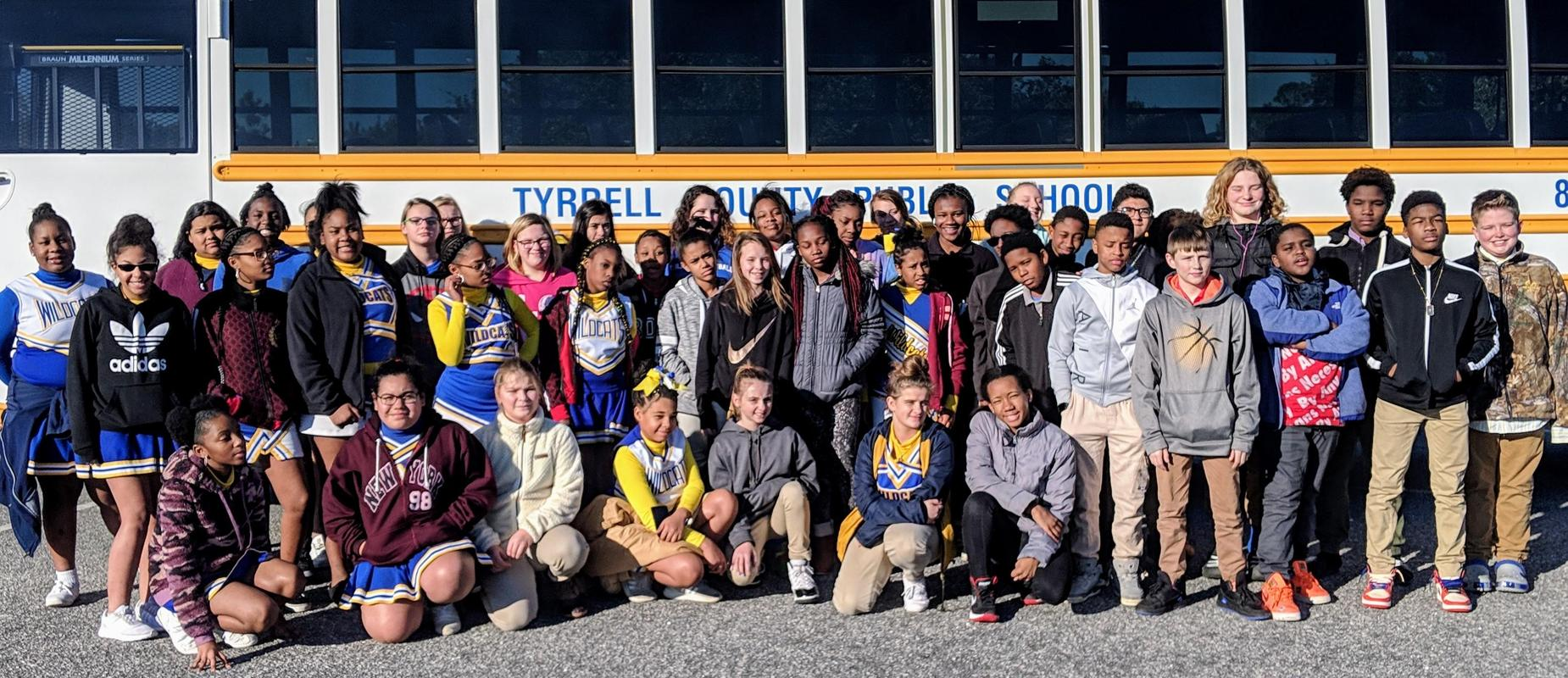 Columbia Middle School students standing in front of a school bus