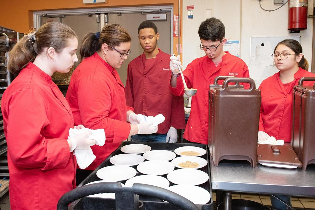 EHS Culinary Arts students, wearing bright red chefs coats, serve bowls of soup