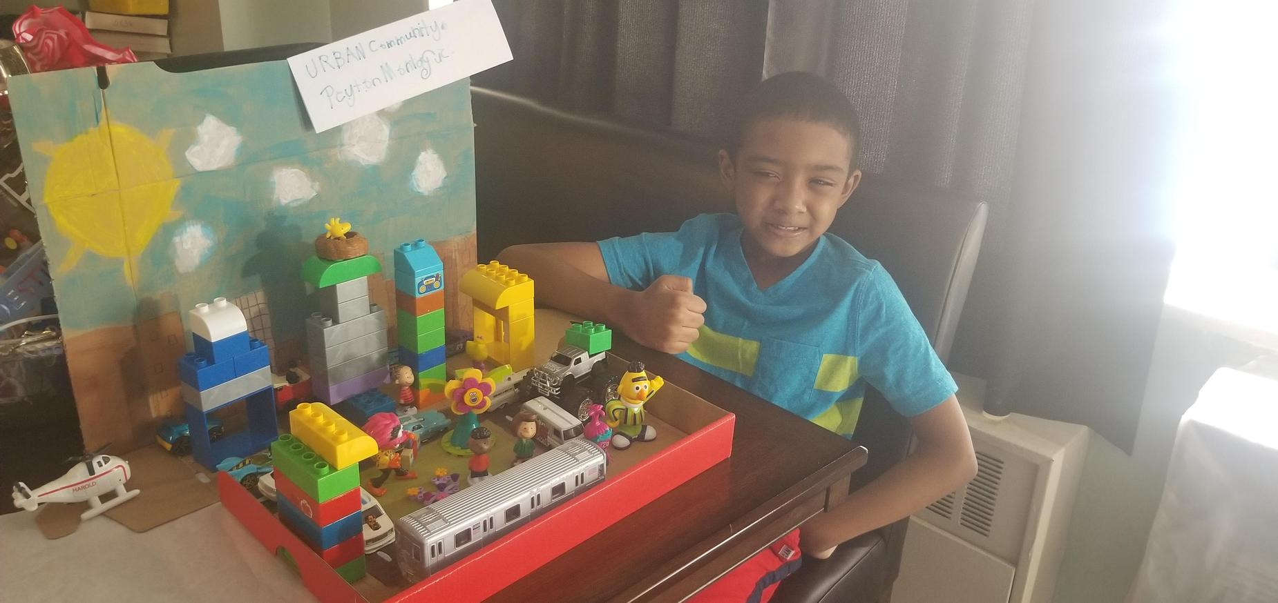 Student sitting  and smiling with a thumbs up, next to a lego urban community