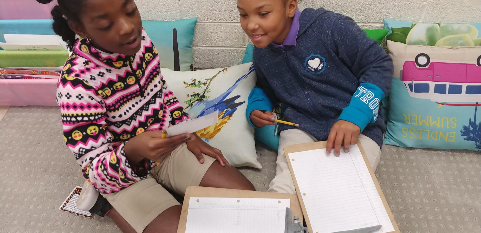 Two students reading from a card.