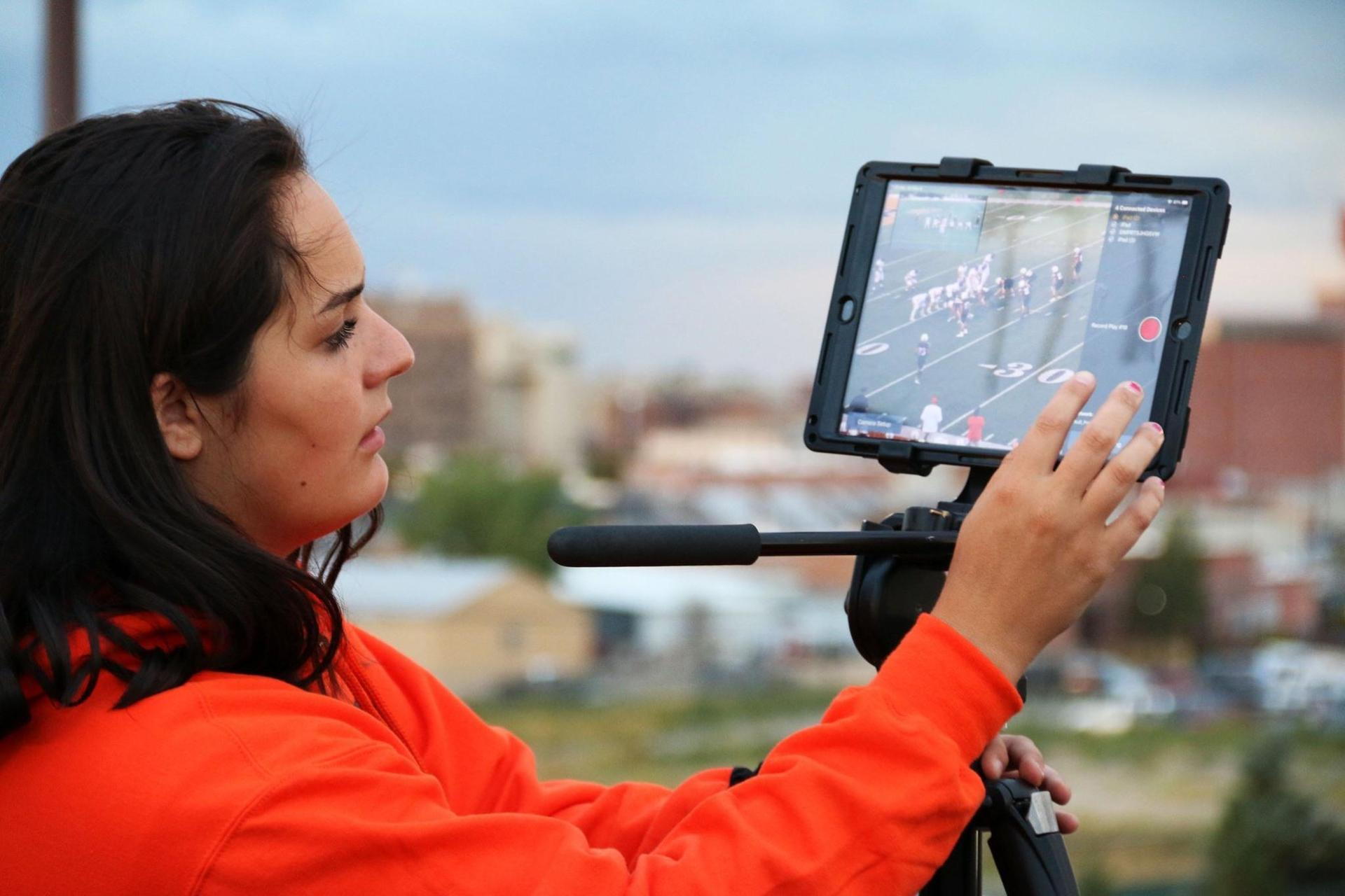 Girl working with video equipment at football game