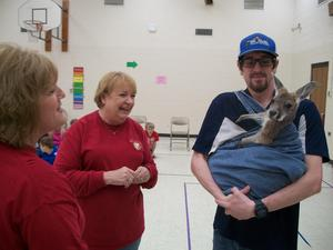 Two teachers look at baby Red Kangaroo in bag pouch.