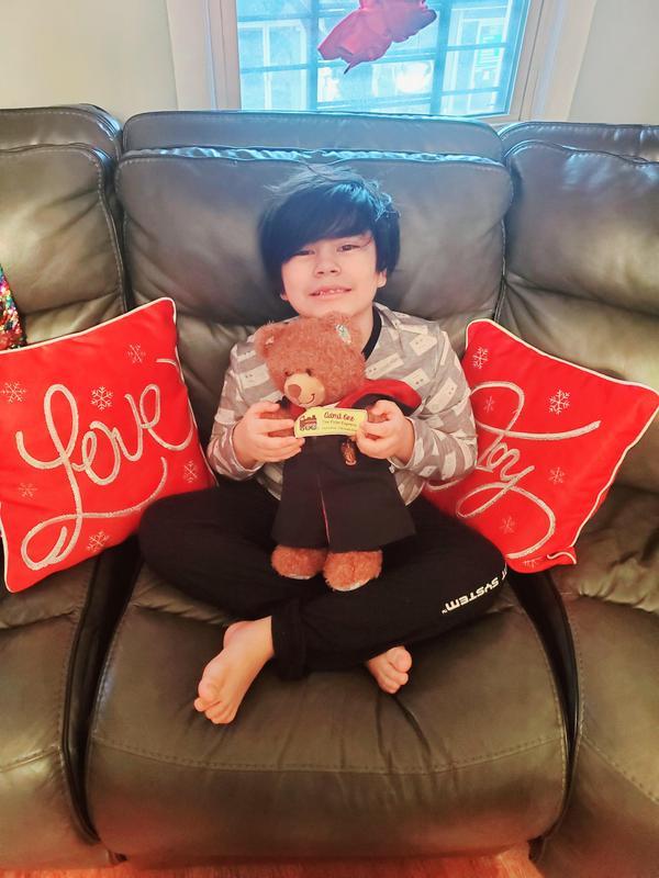 Boy sitting on couch with teddy bear