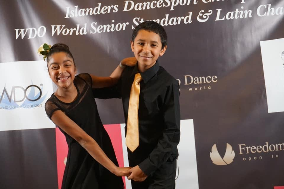 boy and girl standing in front of the Islander DanceSport Championship Banner