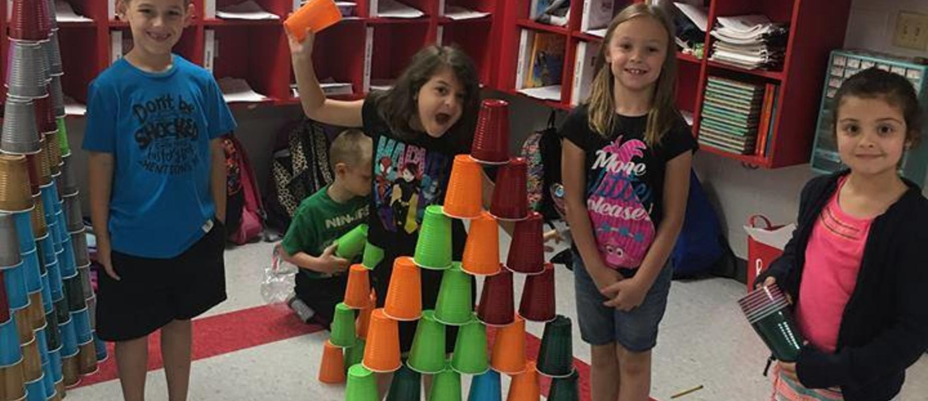 Students building cup towers