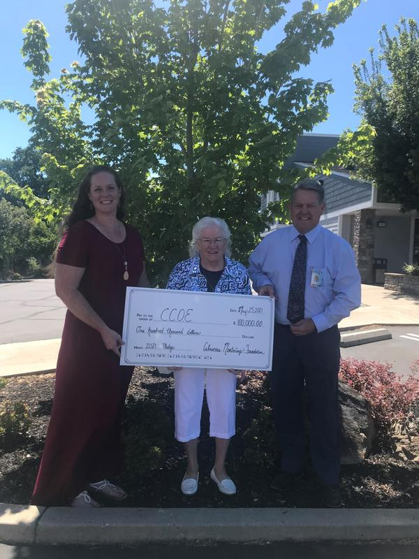 two women and man receiving giant check