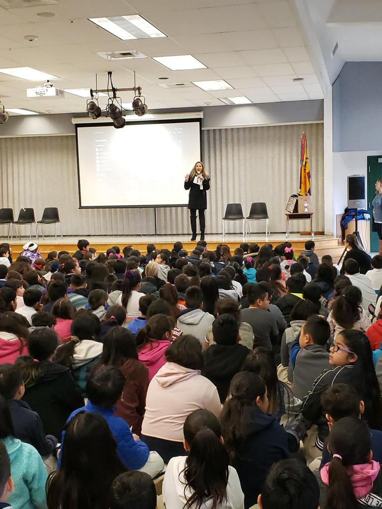 Ms. Reyes stands on stage to introduce Read Across America assembly as students listen from floor