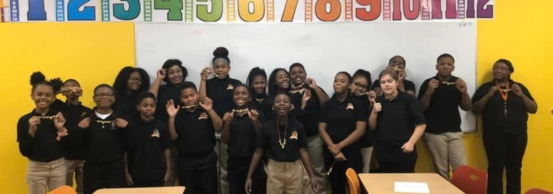 A class of middle grades scholars in matching black DIA polos showing their new necklaces