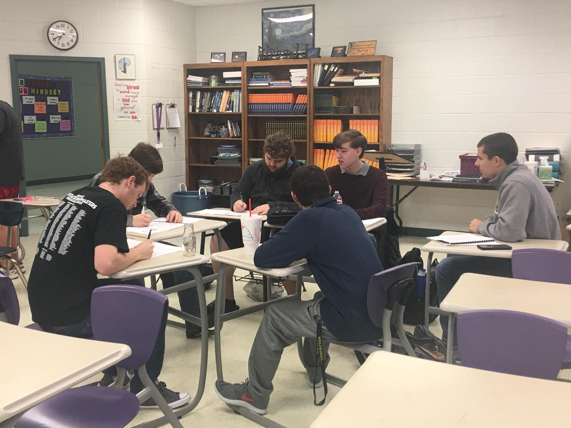 six students sitting in their desks in a circle having a discussion