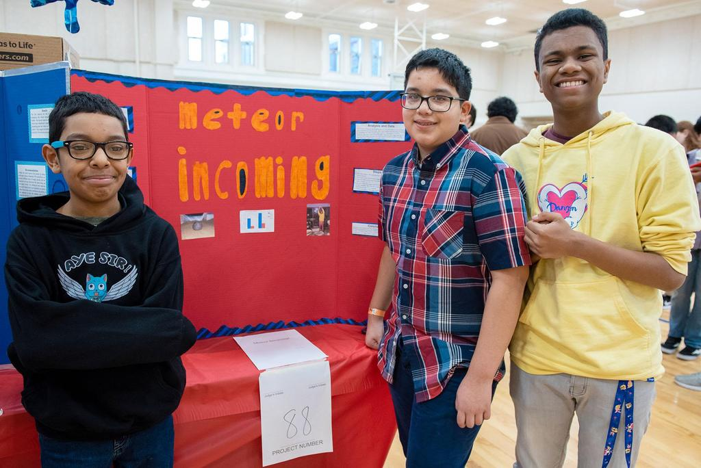Posed photo of three students in front of their project called meteor incoming