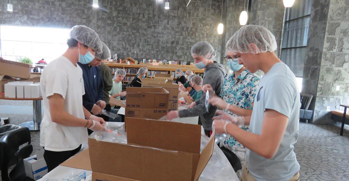 Student volunteers help package items for Kids Food Basket.