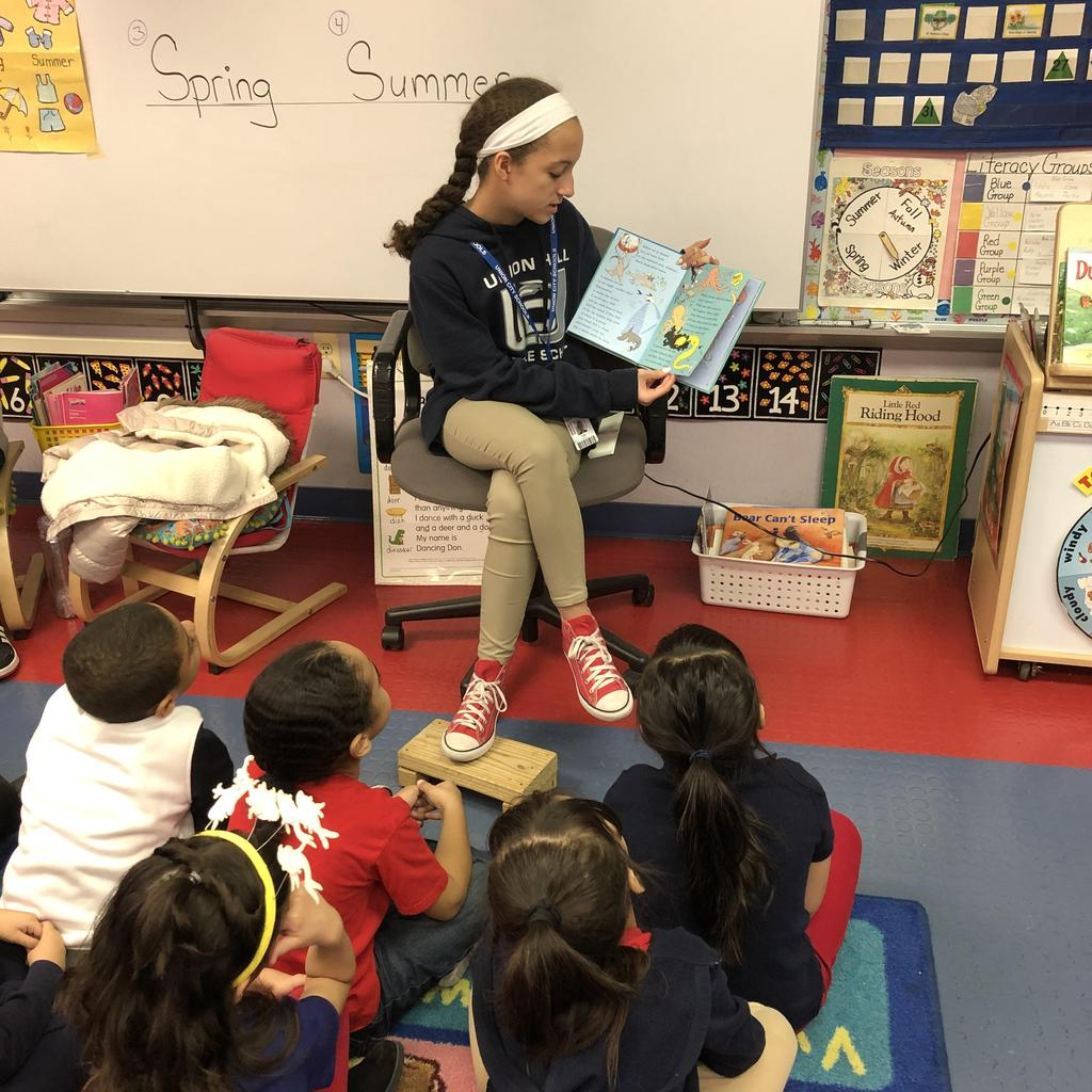 girl with braid reading to students seated on the class rug