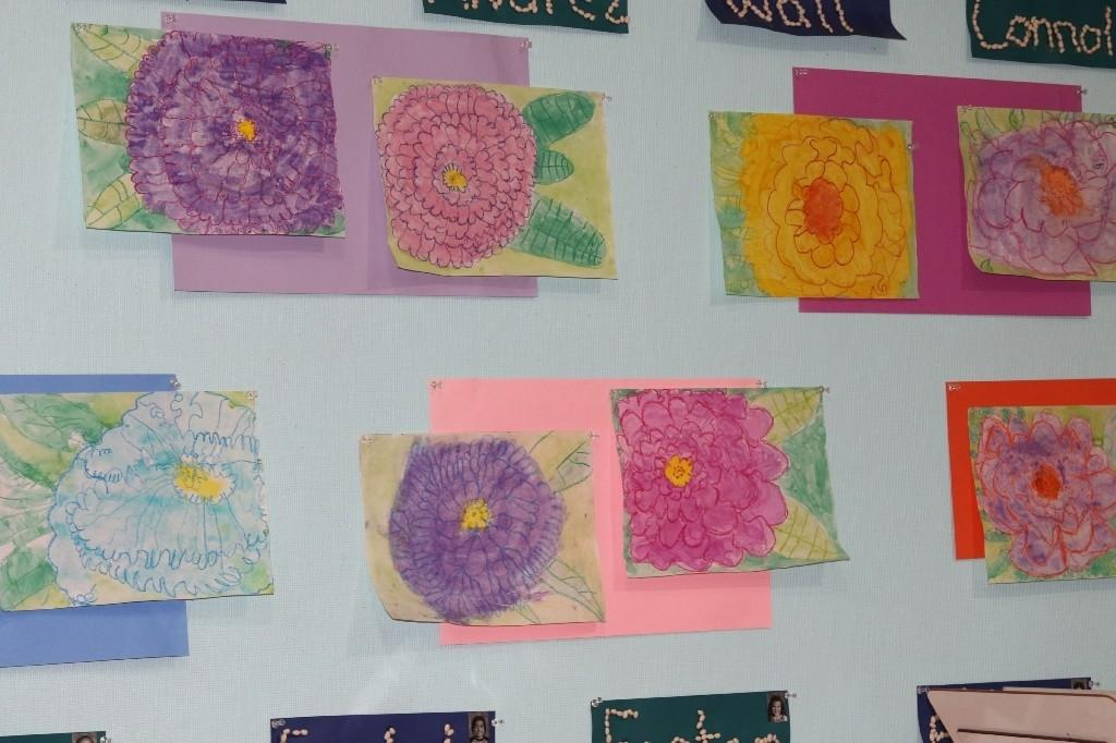 Student art project of flowers displayed on a wall