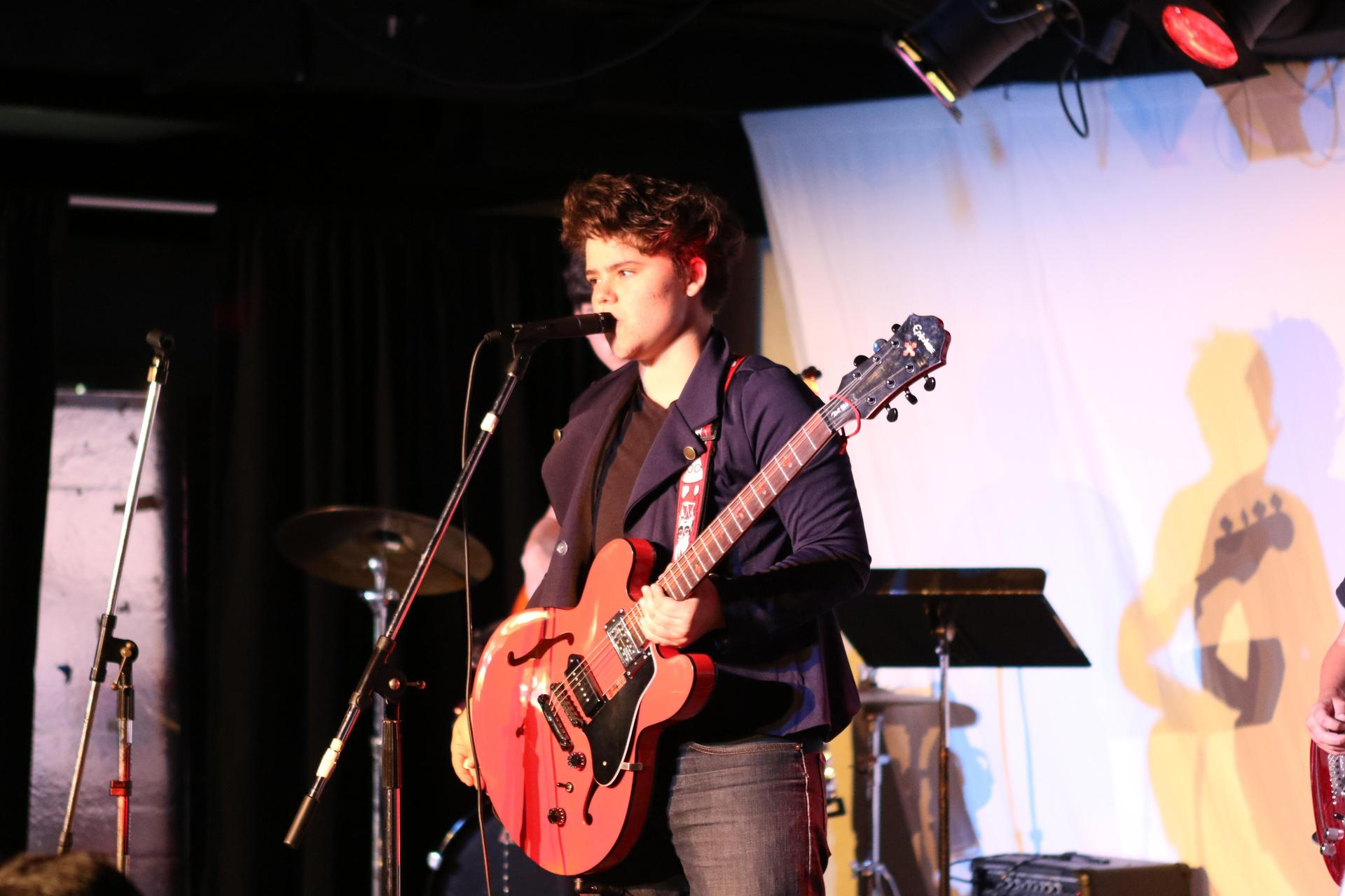 Music student performing with garage band.