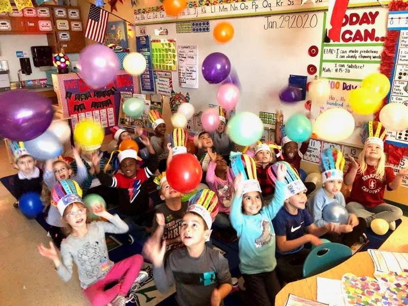 students seated on their classroom carpet wearing handmade crowns playing with balloons