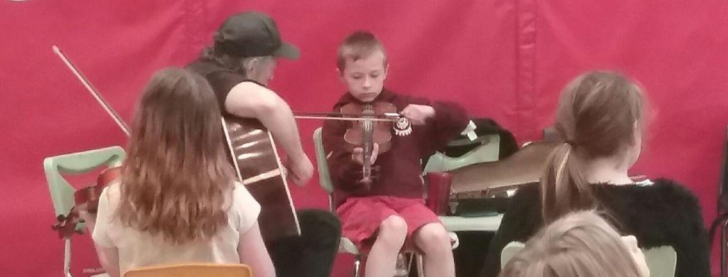 Kelly Thibodeaux, Artist in Residence, teaching Territorial students the fiddle.