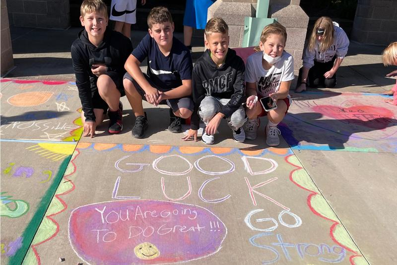 students pose with their chalk mural
