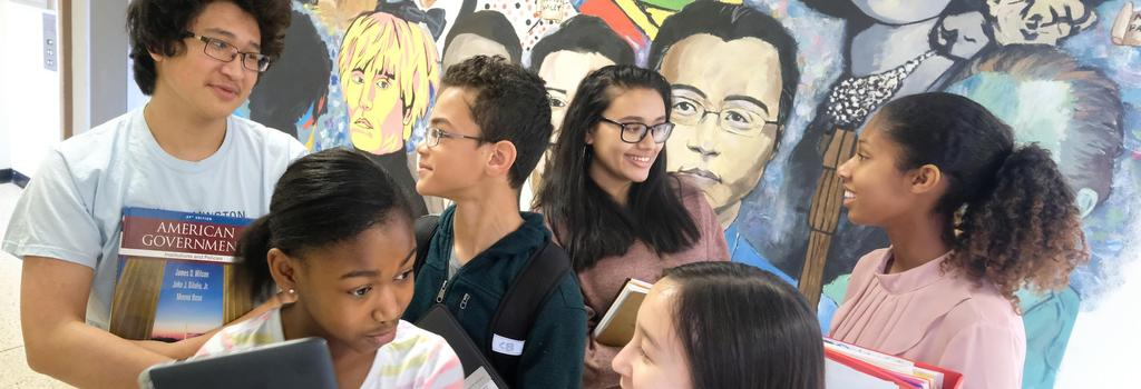 Students in front of mural looking at each other