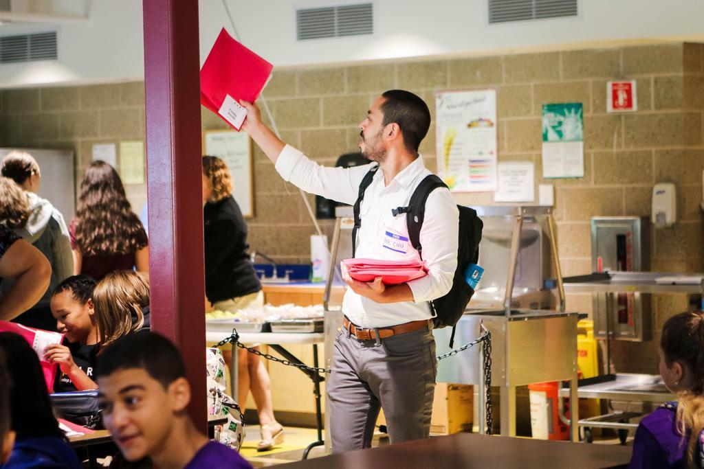 Teacher hands out folders