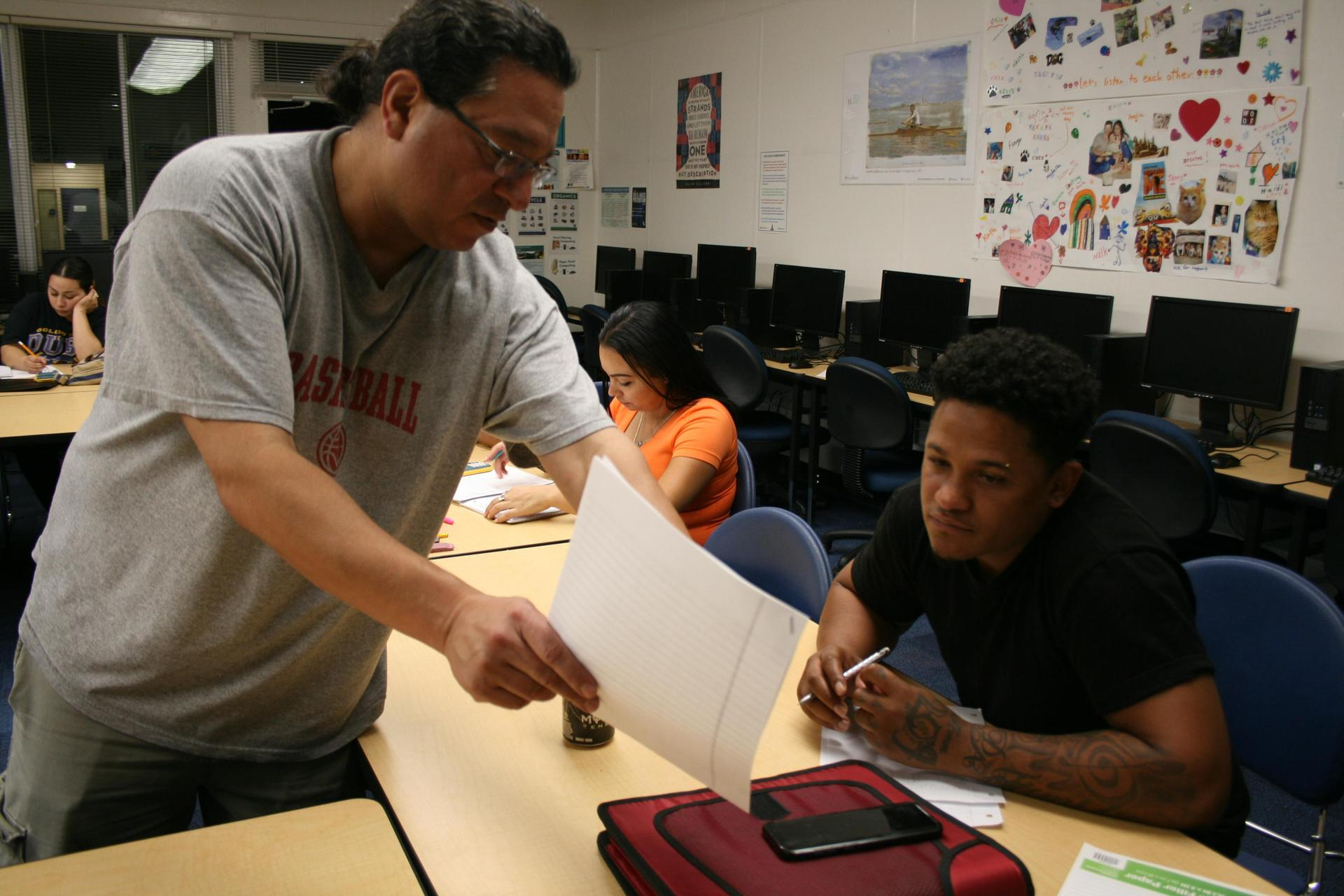 A teacher, standing on one side of a table, points to something on a paper that he is showing to an adult student sitting at the table.