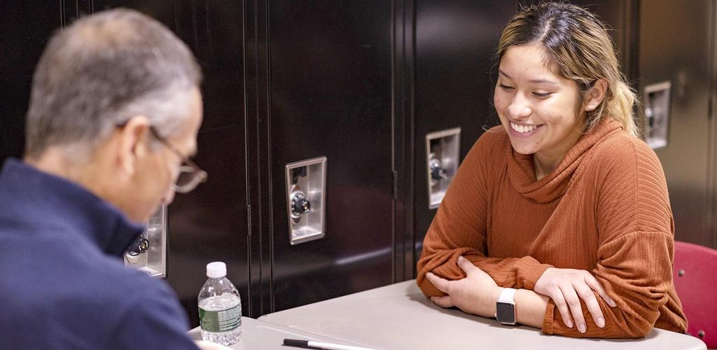 A student smiles and crosses her arms as she's seated at a desk being interviewed