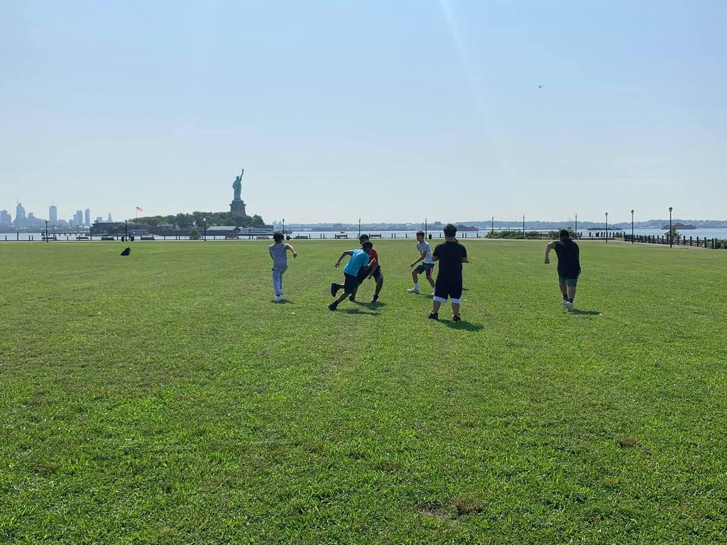 boys playing at the Hoboken Waterfront field with the statue of Liberty in the background