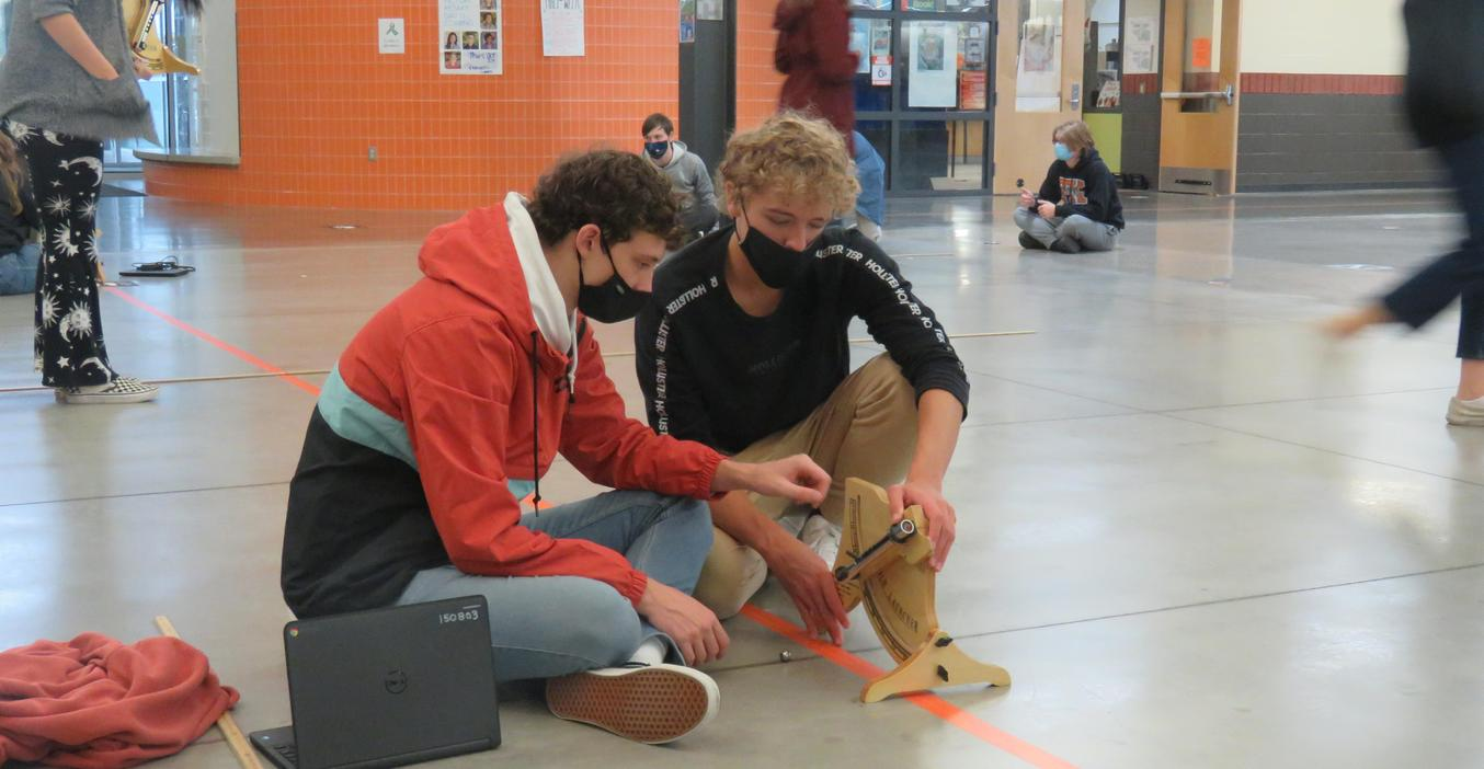 HS students test theories of propulsion and angles with a marble shooter.