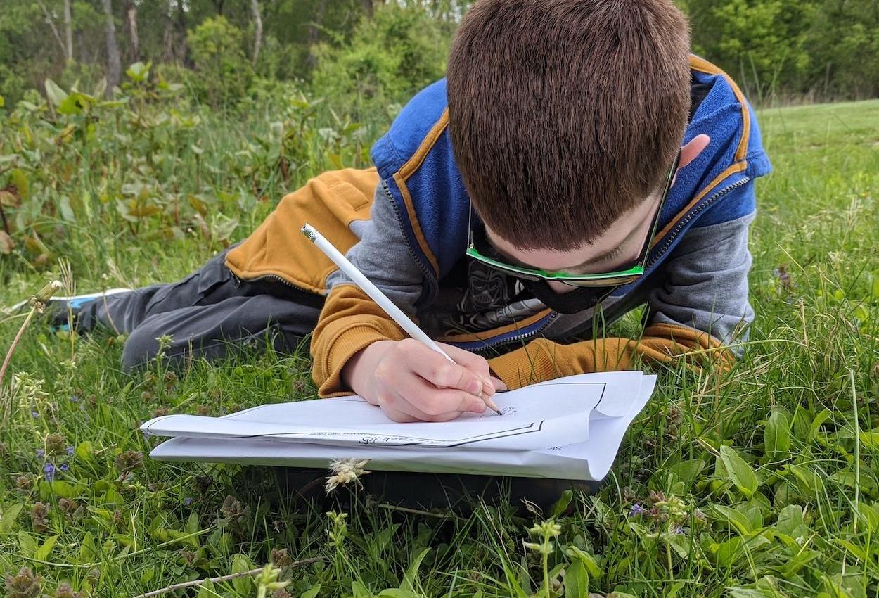 student laying in grass for a lesson