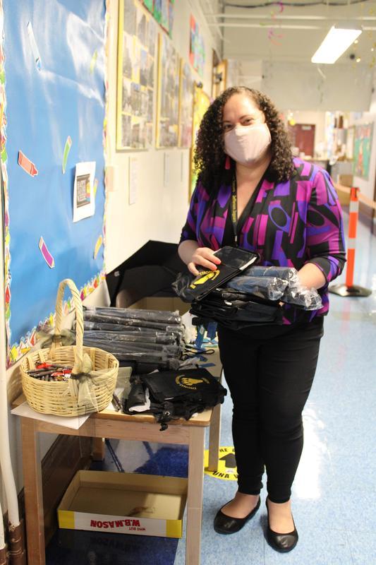 Solangie Ramirez holding merch in hallway