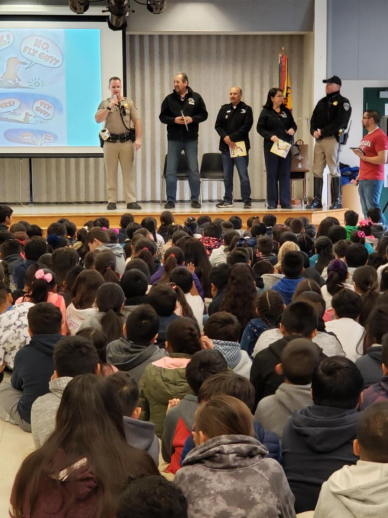 police officers and representatives for Shop with a Cop read to students from stage