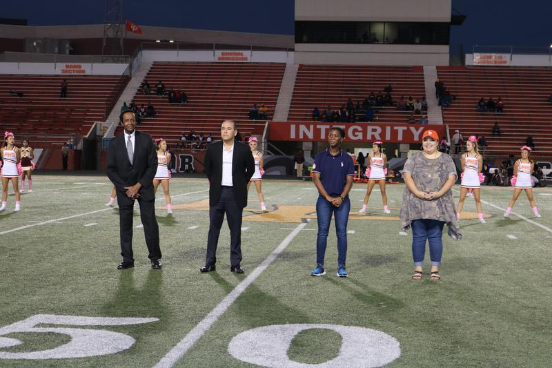 Two men and two women standing on football field