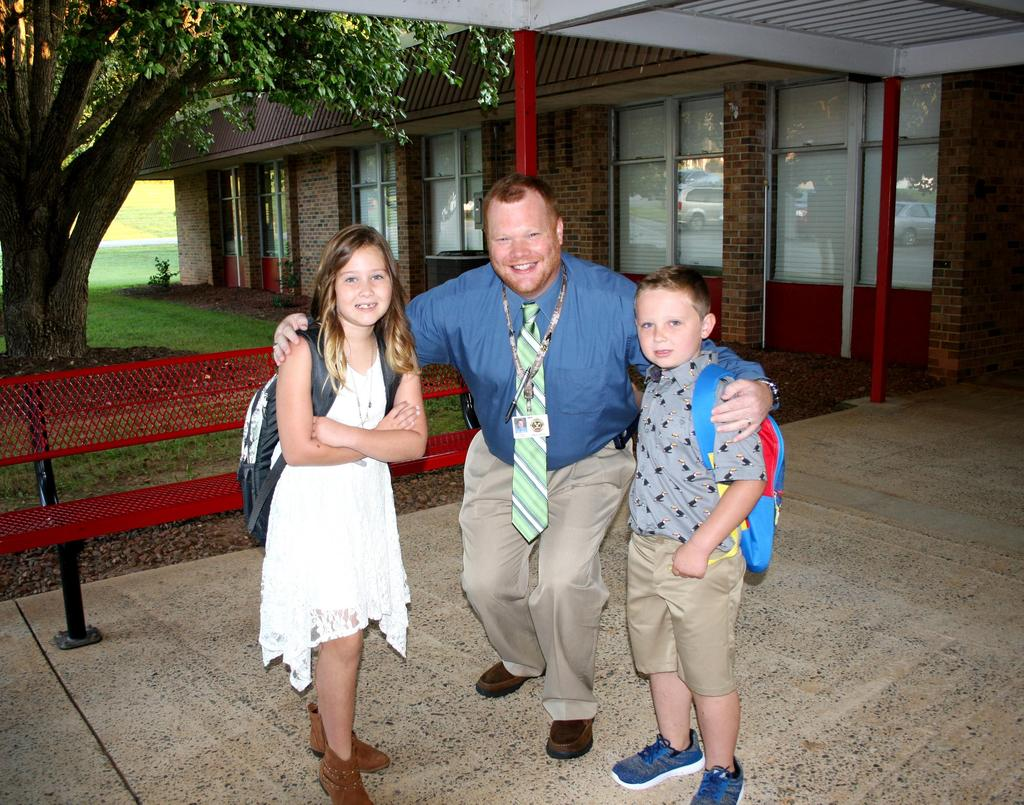 Principal poses with two students on the first day of school at C.B. Eller Elementary.