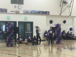 students in Leadership Club standing by balloons with one student speaking into a microphone leading a rally